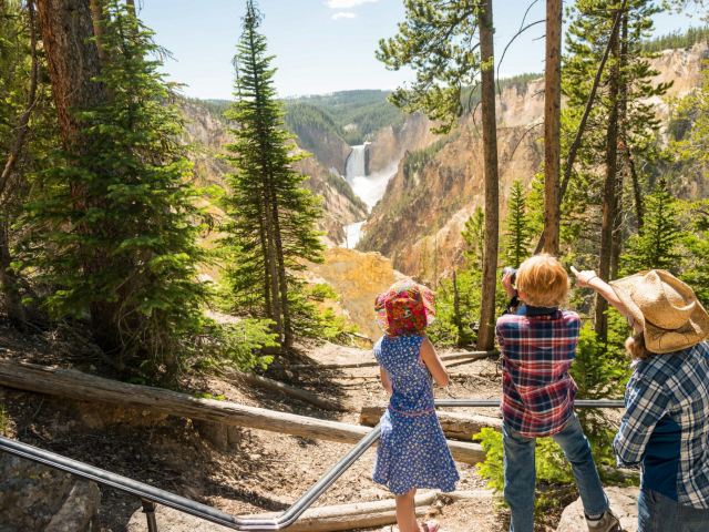 A family gets a photo of the beautiful Yellowstone Falls