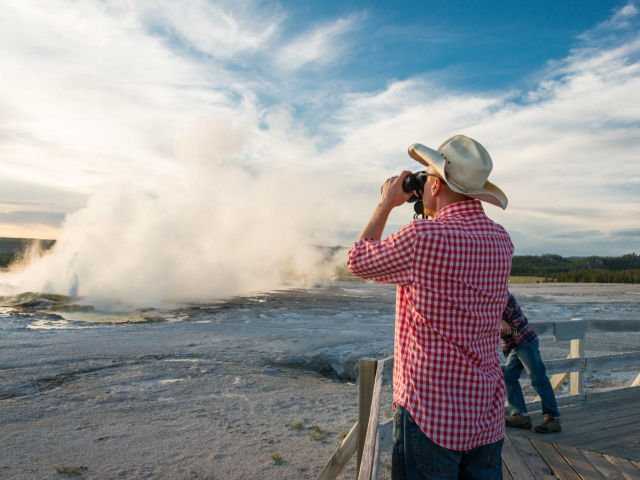 A guest views one of the many geysers found in Yellowstone