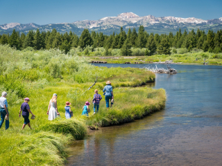 A family hikes along the river in Yellowstone NP